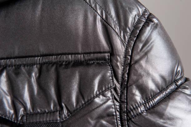 ダウン ジャケット暗闇の中で胸ポケットのクローズ アップ - ダウンジャケット ストックフォトと画像