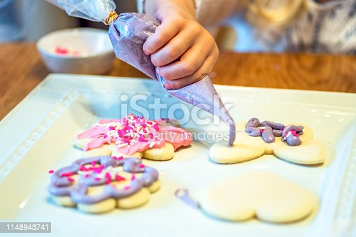 Closeup of child decorating sugar cookies with piping bag filled with purple frosting