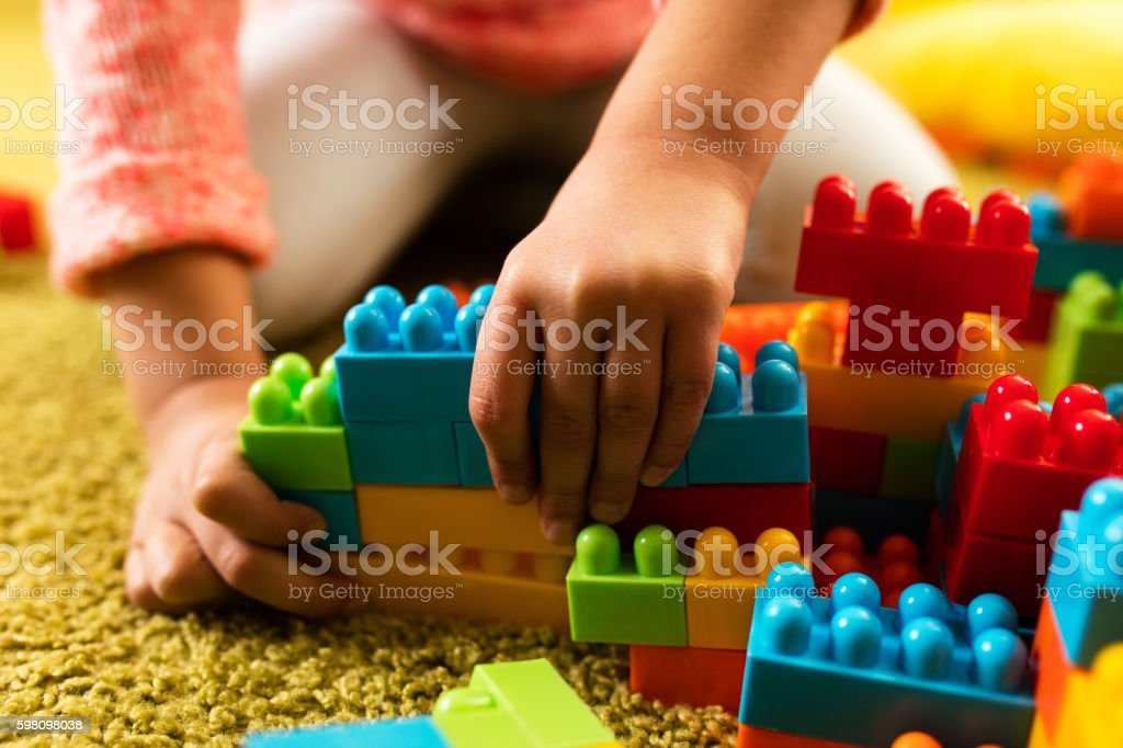 Close-up of child playing with toy blocks on the carpet. stock photo