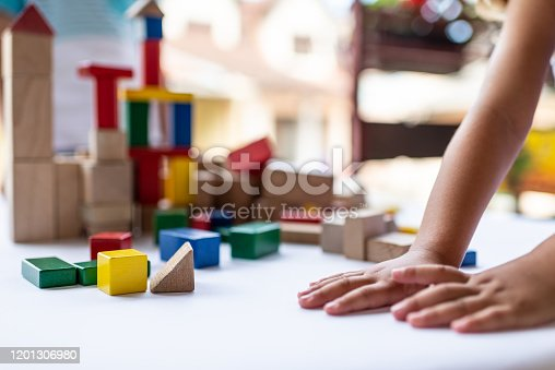 Close-up of a children hands playing with colorful building blocks.
