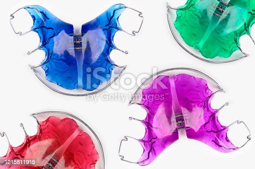 Close-up of children's orthodontic appliances in bright, fun colours on a white table. Concept of oral health in childhood.