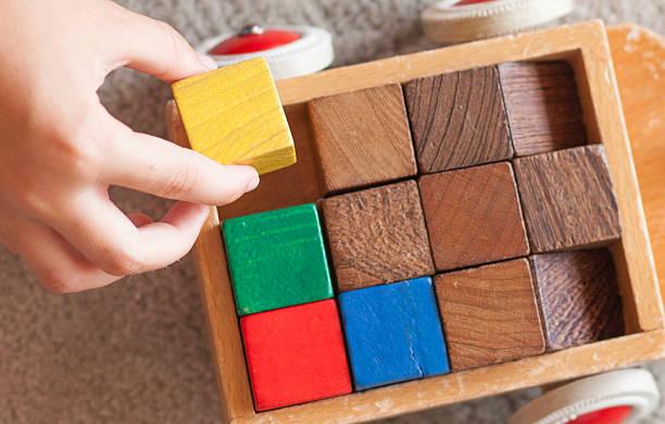 Closeup of child's hand putting wood blocks in small wagon stock photo