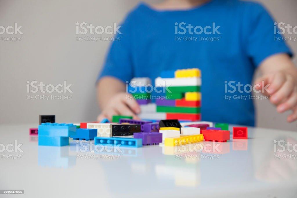 Nahaufnahme des Kindes Hände spielen mit bunten Plastikziegelsteine am Tisch. Kleinkind mit Spaß und aus hellen Konstruktor Ziegeln bauen. Frühes lernen. Streifen-Hintergrund. Entwicklung von Spielzeug. – Foto