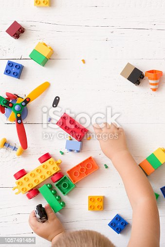 istock Closeup of child's hands playing with multi-color plastic bricks on white wooden background. Toddler having fun and building out of bright constructor bricks. Early learning. Developing toys 1057491484