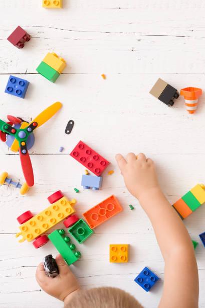 nahaufnahme des kindes hände spielen mit multi-color plastikziegelsteine auf weißem hintergrund aus holz. kleinkind mit spaß und aus hellen konstruktor ziegeln bauen. frühes lernen. entwicklung von spielzeug - wachstumstabelle baby stock-fotos und bilder