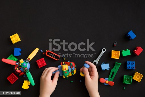 istock Closeup of child's hands with colorful plastic bricks and details of toys on black paper background. Boy or girl playing with parts of bright small spare parts for toys on black table surface 1128863040
