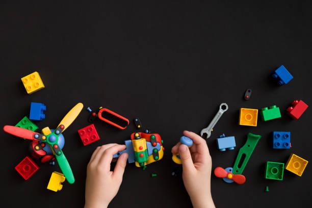 nahaufnahme der hände des kindes mit bunten plastikziegelsteine und details von spielzeug auf schwarzem papierhintergrund. junge oder mädchen spielen mit teilen des hellen kleinen ersatzteilen für spielzeug auf schwarzer tischfläche - wachstumstabelle baby stock-fotos und bilder