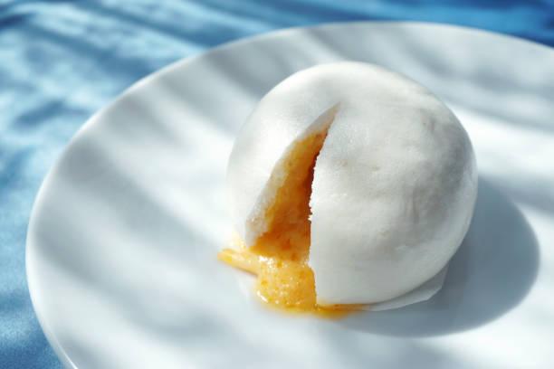 nahaufnahme von chinesische gedämpfte brötchen oder chinesisch gedämpft eigelb pudding lava brötchen auf weißen teller - traditionelle chinesische dim-sum, selektiven fokus. - semmelknödel stock-fotos und bilder