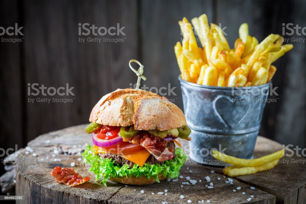 Closeup of chips and hamburger with bacon, tomato and beef stock photo