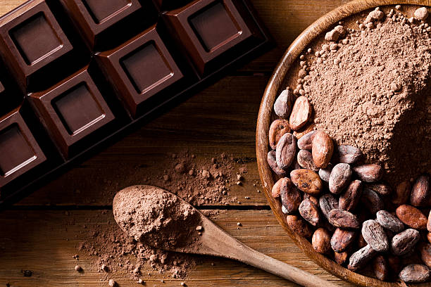 close-up of chocolate bar, cocoa beans and ground cocoa - theobroma stockfoto's en -beelden