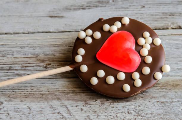 close-up of chocolate lollipop with heart jelly - lutscher cookies stock-fotos und bilder