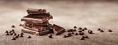Slices of dark chocolate with chocolate chips on brown background close-up. Long wide banner