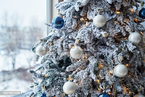 istock Closeup of Christmas tree decorated with white baubles and garland near window, copy space. Christmas decorations. Holiday background. Christmas tree. Greeting card 1057901326