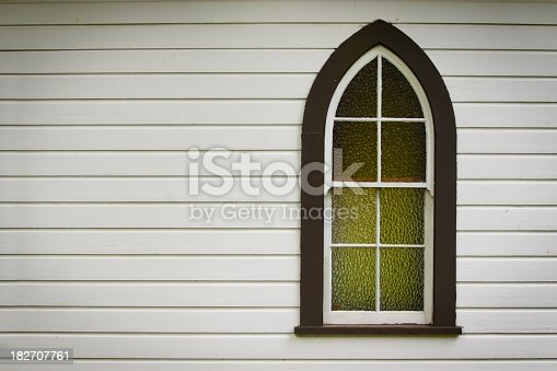 A single church window in an historic pioneer church, offset with plenty of copy space.