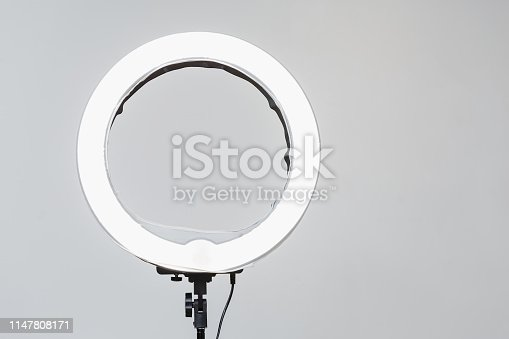 Closeup of circular neon LED lamp at white background. Popular modern light for make-up and beauty portraits