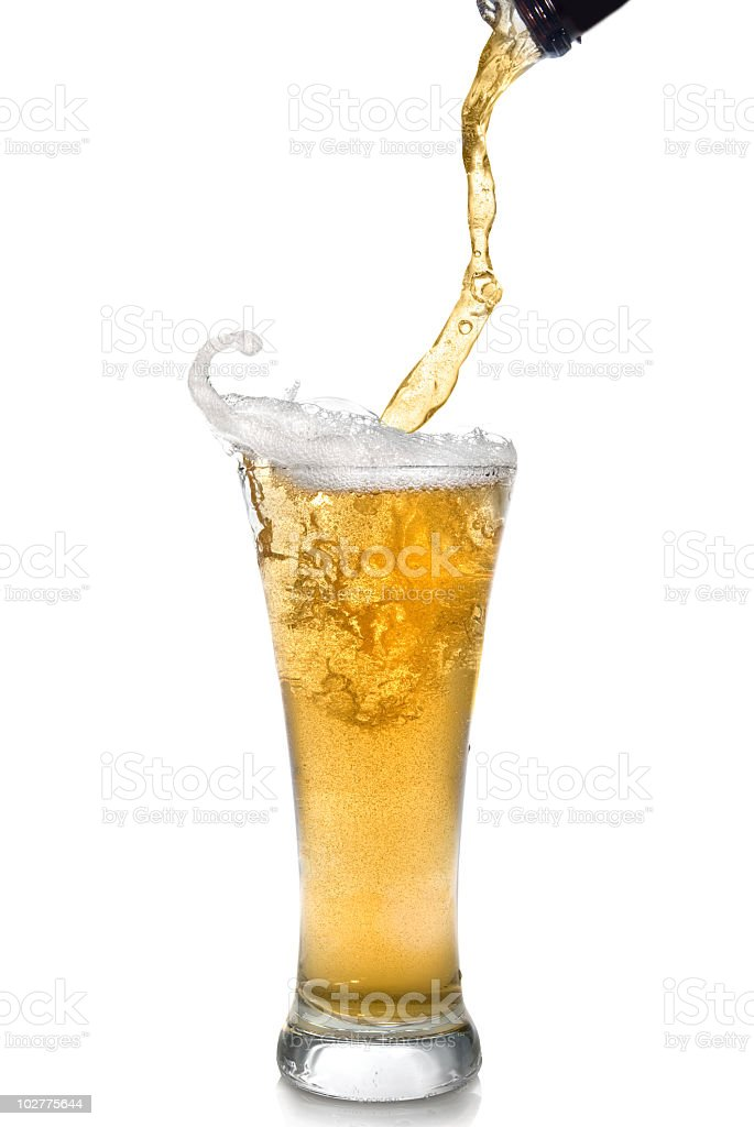 Close-up of clear beer pouring from bottle into a glass stock photo
