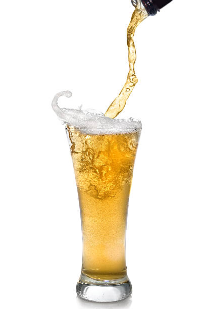 close-up of clear beer pouring from bottle into a glass - beer pour stock photos and pictures
