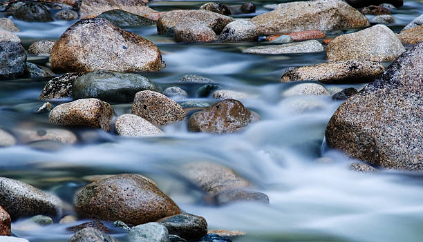 close-up of clear water flowing through pebbles in stream - river stock photos and pictures