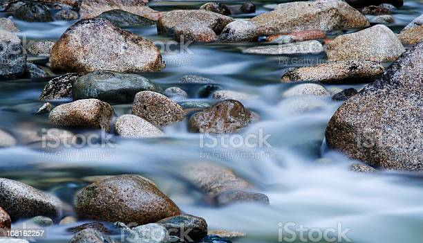 Photo of Close-up of clear water flowing through pebbles in stream