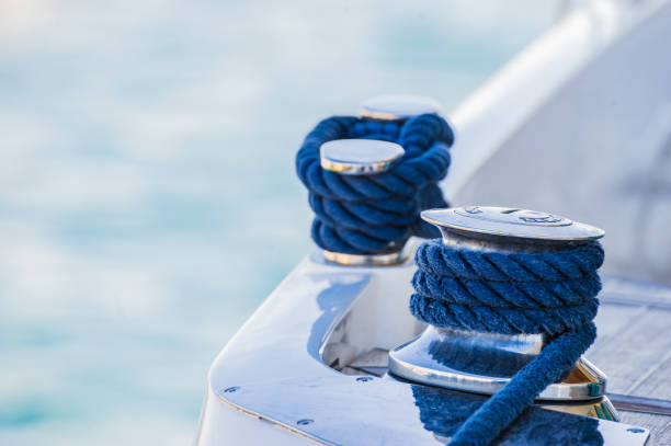 Close-up of cleat and nautical rope on modern motor yacht deck Detail view of motorboat yacht rope cleat on boat deck mooring stock pictures, royalty-free photos & images