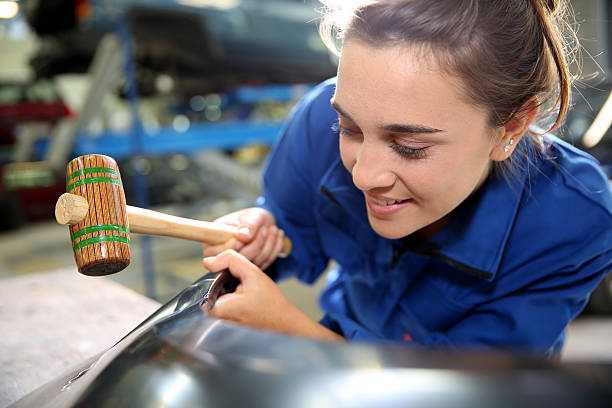 Closeup of coachbuilder with mallet in hands stock photo