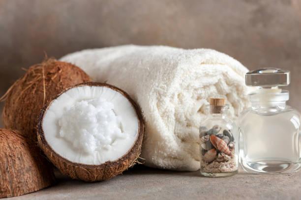 Close-up de Coco, toalhas macias, essência de coco, creme de coco e conchas. Conceito de Spa, salão de beleza e saúde, loja de cosméticos. - foto de acervo