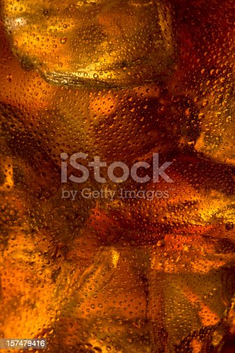 Close up of ice floating in a glass of cola. Detailing shows condensation and melting ice along with the refreshing bubbles in the drink itself.