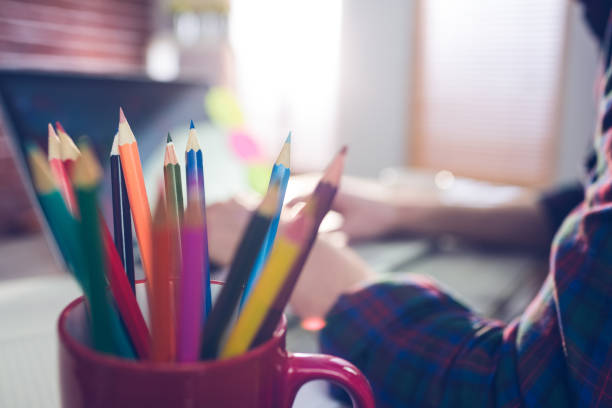 Close-up of colored pencils in mug Close-up of colored pencils in mug with businessman working in background design occupation stock pictures, royalty-free photos & images