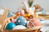 Festive composition of small basket with colorful Easter eggs painted with polka dots or stripes, blurred background of beautifully decorated table