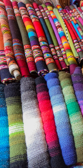 Close-up of colorful indigenous hand-woven scarves in a market in Chincero, Peru