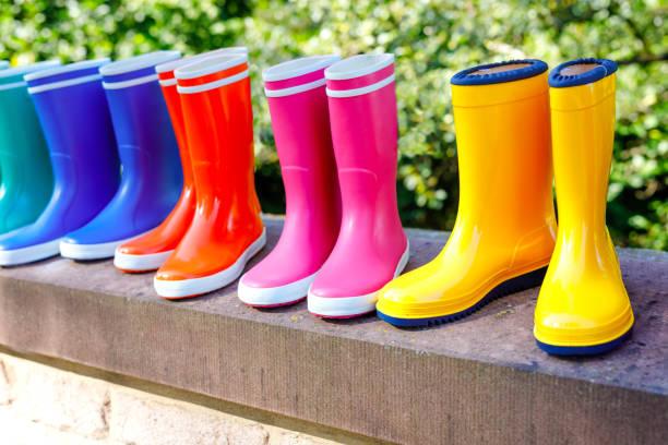Nahaufnahme von bunten Regenstiefeln für Schul-und Vorschulkinder im Herbstwald. Nahaufnahme verschiedener Gummistiefel. Schuhe und Mode für regnerischen Herbst. – Foto