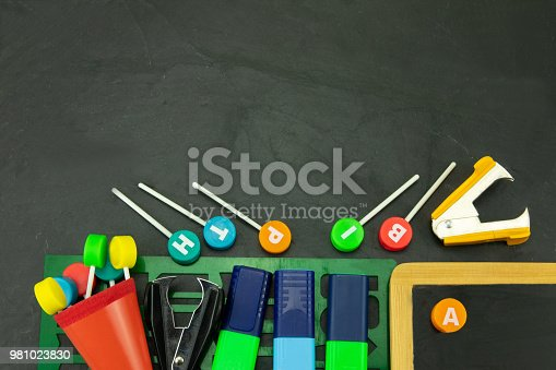 istock Closeup of colorful school supplies with copy space on blackboard background. Back to school. 981023830