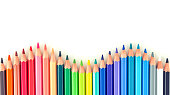 Closeup of coloured pencils lined up in a row on white background copy space