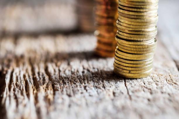 Nahaufnahme der Säulen der Goldmünzen auf der alten Holzplatte – Foto