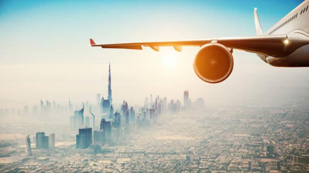 nahaufnahme von kommerziellen flugzeug fliegt über moderne stadt - vereinigte arabische emirate stock-fotos und bilder