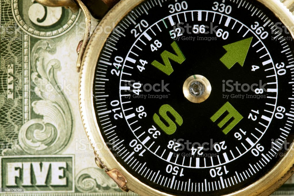 Close-up of Compass Lying on Five Dollar Bill royalty-free stock photo