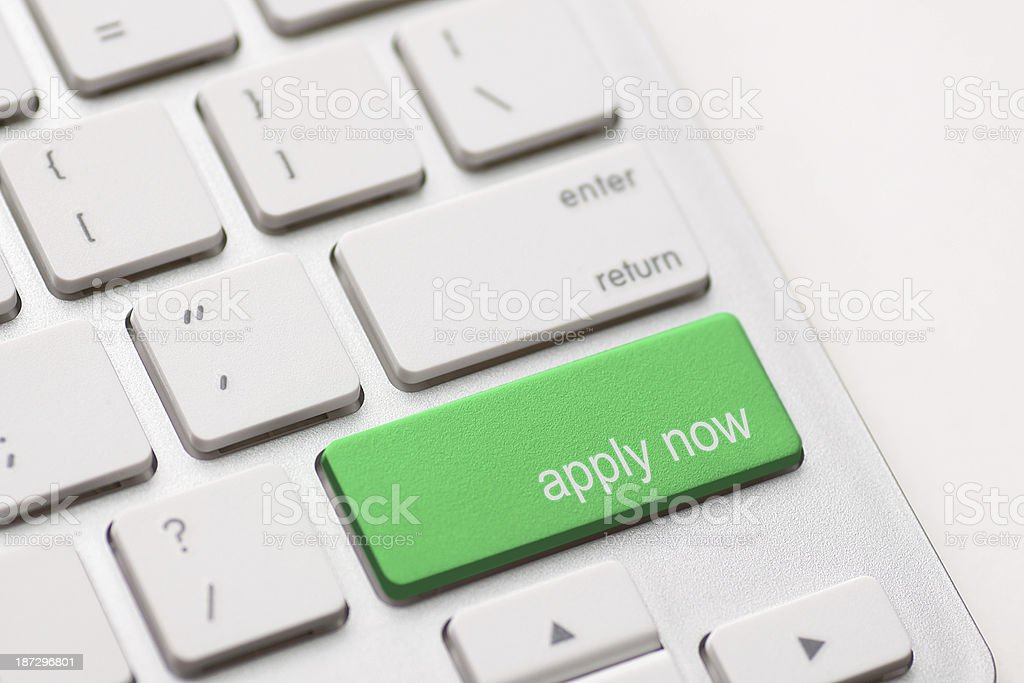 Close-up of computer keyboard with a green apply now button stock photo