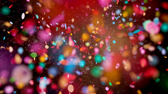 Close-up of multi coloured confetti flying mid-air against black background.
