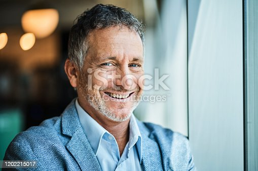 Close-up portrait of confident male entrepreneur. Smiling mature businessman is at coworking space. He is in suit.