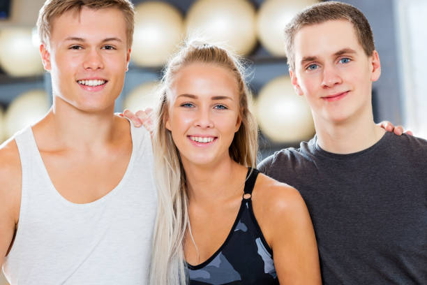 Close-up of Confident Male And Female Friends Smiling In Gym stock photo