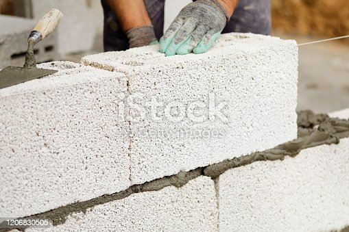 Close-up of construction worker builds brick wall