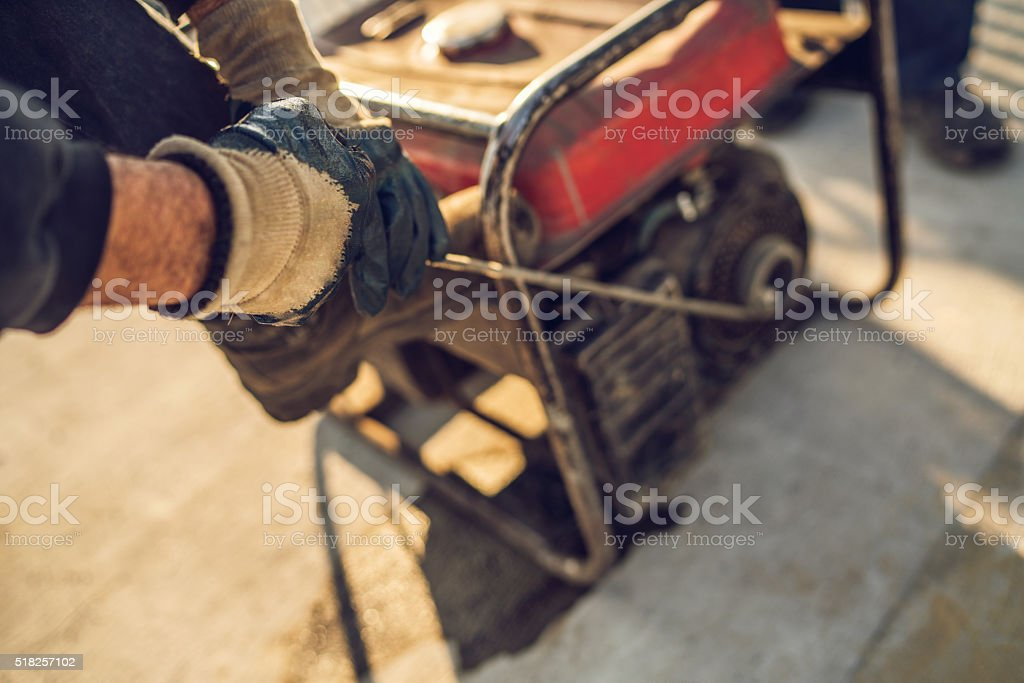 Close-up of construction worker starting power generator. stock photo