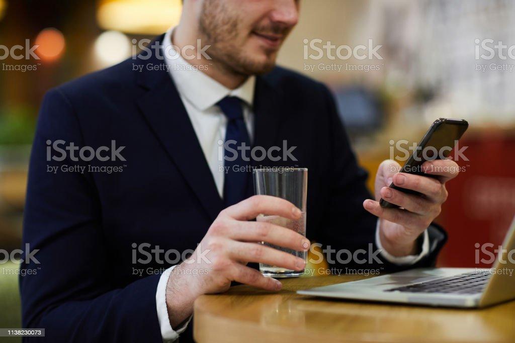 Businessman reading Internet news on smartphone