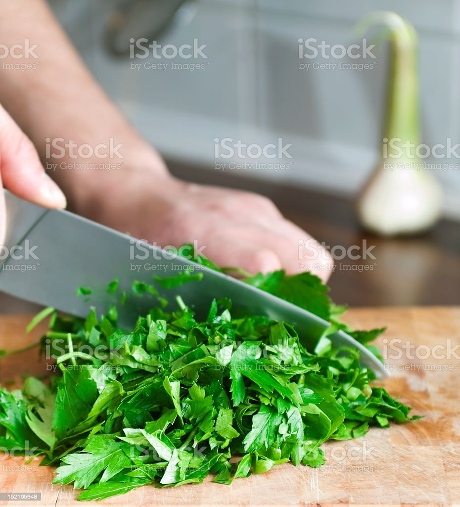 Closeup of cook's hands chopping green herbs with knife stock photo