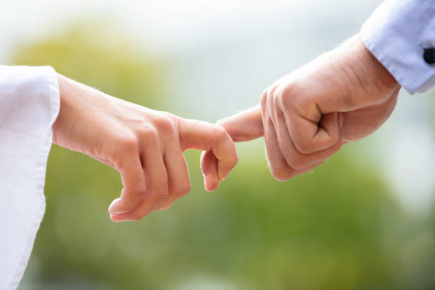 Close-up Of Couple Holding Index Fingers Close-up Of Loving Couple Holding Each Other's Finger Against Blurred Background symbiotic relationship stock pictures, royalty-free photos & images