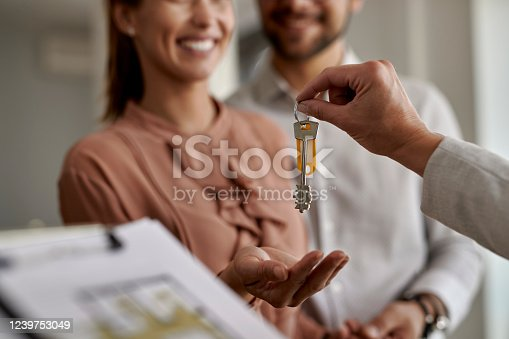 Close-up of real estate agent giving new house keys to a couple.