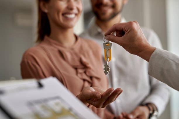 close-up de casal recebendo novas chaves de casa de agente imobiliário. - chave - fotografias e filmes do acervo