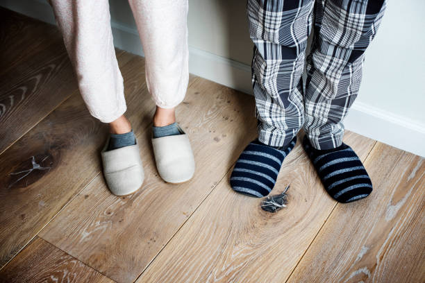 Closeup of couple wearing slippers on wooden floor stock photo
