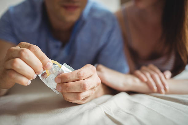 close-up of couple with a condom on bed - rubber stockfoto's en -beelden