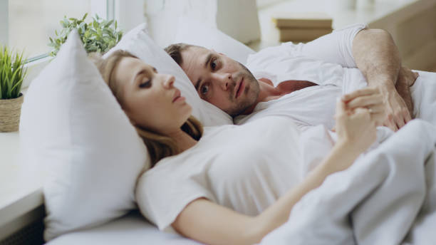 Closeup of couple with relationship problems having emotional conversation while lying in bed at home Closeup of couple with relationship problems having emotional conversation while lying in bedroom at home husband stock pictures, royalty-free photos & images